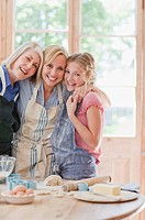 Smiling multi_generation females hugging and baking in kitchen