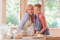 Smiling mother and daughter hugging and baking in kitchen