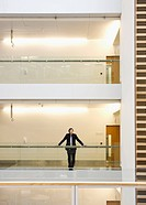 Businessman standing at railing in corridor