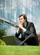 Pensive businessman with laptop sitting cross_legged in grass outside office building