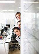 Curious business people peering around corner in office
