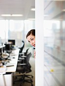 Curious businesswoman peering around corner in office