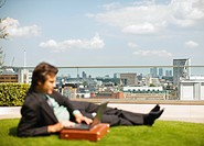 Businessman using laptop on grass overlooking city