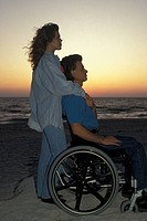 Florida, Napels. Disabled man with woman on the beach at sunset