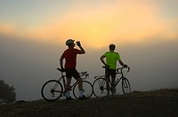 Bicycle riders watching sunset on mountain, Northern California, USA
