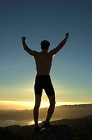 Silhouette of young man on mountain top celebrating victory with arms raised