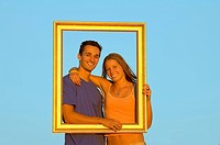 Portrait of teenage couple in gold picture frame