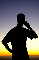 Silhouette on man talking on cell phone at sunset