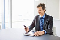 Businessman checking cell phone in conference room