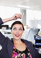 Smiling businesswoman holding light bulb overhead in office
