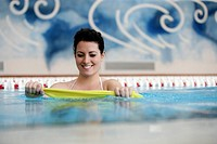 Woman in swimming pool doing pilates exercise