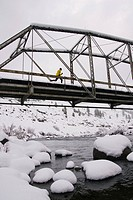 A man running across a trestle brigde on a snowy day near Truckee in California