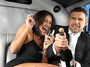 Couple in limousine celebrating. Man uncorking champagne bottle