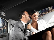 Businessman and businesswoman sitting in the back seat of a limousine flirting