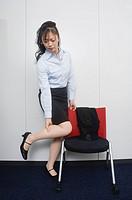 Businesswoman massaging her leg