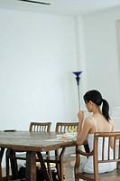 Rear view of a young woman eating breakfast