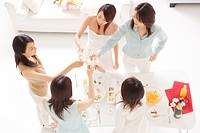 Five young women toasting with glasses of champagne