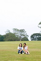 Two young women sitting in park