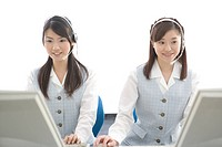 Two young women with headsets working on computer