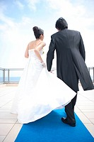 Rear view of bride and groom walking