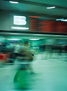 Traveler walking with luggage at airport, blurred motion