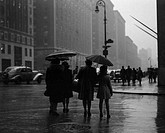 USA, New York State, New York City, People walking through street and holding umbrellas during rainy day