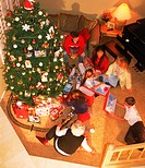 Overview of family and friends around Christmas tree at home exchanging presents