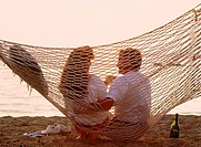 Couple drinking champagne in beach hammock at sunset