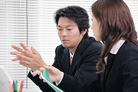 Young woman and mid adult man talking in office