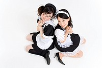 Two young women in French maid outfit smiling