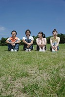 Four young people sitting on grass field