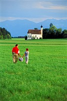 Father and daughter walking with picnic basket across green farmlands in Bavaria, Germany