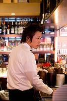 Waiter standing behind bar counter
