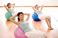 Young women lying on fitness balls doing sit_ups