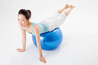 Young woman doing push_ups on fitness ball