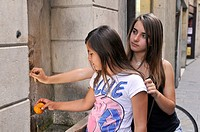 Two girls washing fruit in a font, Girona, Catalonia, Spain, Europe