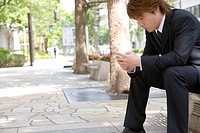 Young businessman looking at mobile phone