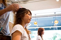 Hairdresser styling young womans hair