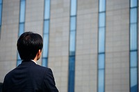 Rear view of a man staring at office building
