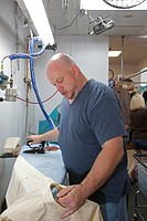 Broomfield, Colorado - A worker at Lionheart Cleaners, a laundry and dry cleaning firm