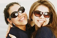 Close_up of two young women hugging each other and wearing sunglasses