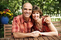 Mature man with his arm around a mature woman and smiling