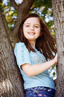 Portrait of a girl sitting on a tree trunk and smiling