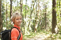 Caucasian woman hiking in forest with backpack