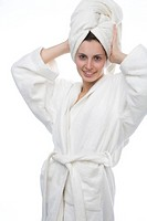 Young woman in bathrobe with a towel wrapped around her head