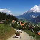 Switzerland, Alps, Engadine, Savognin village, people on karts