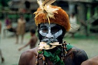 NEW GUINEA, SEPIK RIVER, PORTRAIT OF PRIMITIVE MAN WITH HEADRESS AND PIG TUSK MOUTHPIECE
