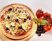 Pizza: olives, courgettes, onions & sweetcorn on wooden plate