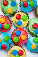 Chocolate cupcakes with coloured icing and chocolate beans