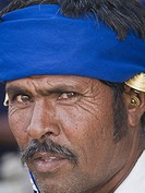Portrait of a man in traditional dress with local ear ings worn by men in Naroda, Gujarat. India